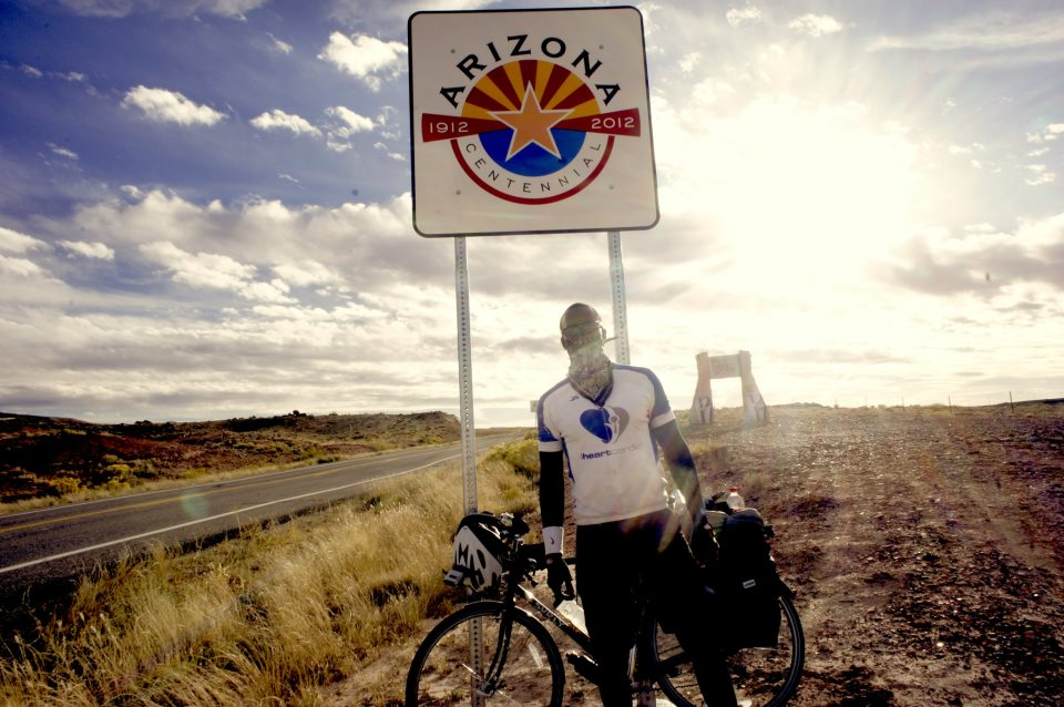 Justin McClelland in front of the Arizona state border sign exiting from colorado and the four corners monument
